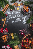 Traditional mulled wine ingredients with cooking pot ,mugs and fir branches on black chalkboard background. Top view, frame stock image