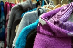 Traditional multi colored woolen knitwear clothes for sale on a market stall.  stock images