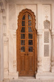 Traditional narrow brown wooden door with ornate stone doorframe Stock Photos