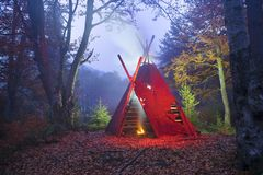 Wigwam tipi and bonfire. The traditional national dwelling of North American Wigwam Indians, typified by the background of an old wild beech forest at night, at Stock Photos