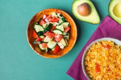Traditional National Mexican Tomato Rice Stewed Pilaf with Hot Chili Peppers Garlic in Bowl. Fresh Cucumber Onion Salsa Avocado. Traditional National Mexican stock photo