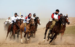 Traditional national nomad horse riding. AKCHI, KAZAKHSTAN - MARCH 22 : A traditional national nomad long-distance horse riding competition Bayga in action on Royalty Free Stock Photo