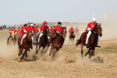 Traditional national nomad horse riding. AKCHI, KAZAKHSTAN - MARCH 22 : A traditional national nomad long-distance horse riding competition Bayga in action on Stock Image