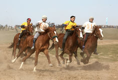 Traditional national nomad horse riding. AKCHI, KAZAKHSTAN - MARCH 22 : A traditional national nomad long-distance horse riding competition Bayga in action on Royalty Free Stock Photography