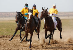 Traditional national nomad horse riding. AKCHI, KAZAKHSTAN - MARCH 22 : A traditional national nomad long-distance horse riding competition Bayga in action on Stock Photo
