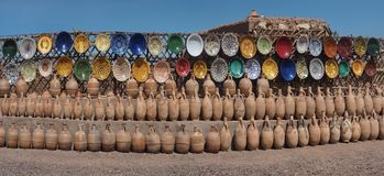 Traditional North African ceramics, colorful colorful dishes and clay brown jugs, photo panorama, Morocco. Traditional North African ceramics: colorful colorful Stock Image