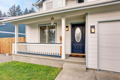 Traditional northwest home with navy blue door and white fencing Stock Image