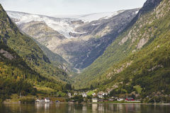Traditional norwegian fjord village with glacier. Hardanger rout Stock Image