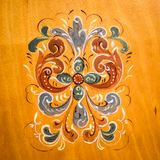 Traditional Norwegian Folkart Rosemaling Painting. A traditional Norwegian Folkart Rosemaling Painting on a wooden background with blue, red, green and white as royalty free stock photography
