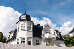 Traditional Norwegian house. The white wooden house with copper roof on the blue sky background Stock Images