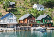 Traditional Norwegian houses, blue water and green colors of nature royalty free stock image