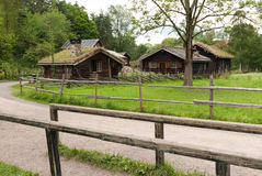 Traditional Norwegian houses. The old wooden houses with dirt roof on the green trees background Stock Photo