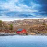 Traditional Norwegian red wooden boat barn with crane. On the seacoast Royalty Free Stock Image