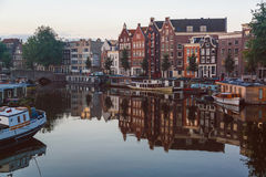 Traditional old buildings and canal with private boats in Amsterdam, the Netherlands Royalty Free Stock Images