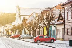 Traditional old buildings and parked cars in the street, Kezmaro. K city, Slovak republic. Travel destination. Yellow sun rays scene Royalty Free Stock Photos