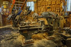 Traditional old clog making machine in workshop with wooden shoes on display royalty free stock images