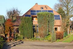 Ancient house with modern alternative solar panels, Netherlands. Traditional old house with the modern technology of solar panels at the roof, Netherlands Stock Photos
