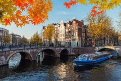 Traditional old houses on canal at fall day in Amsterdam, Nether stock photos