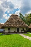Romanian country house. Traditional old romanian country house with thatched roof with nice cloudy blue sky on background royalty free stock image