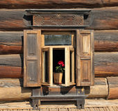 Traditional old russian window. Ornamental window of the old rural house with flower. Suzdal, Gold Ring, Russia Royalty Free Stock Photo