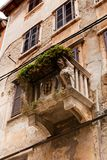 Facade of an old house with a stone balcony decorated with lion heads stock photos