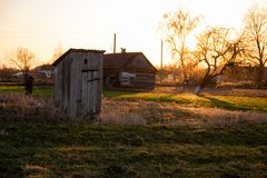 Traditional old wooden WC outhouse in the garden in summer royalty free stock photography