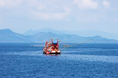Traditional orange thai fishing boat floating in the bay of thailand near koh chang on day the bright sky stock image