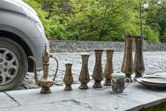 Traditional Oriental brass handmade jugs with tradiitional ornament for sale by a street vendor on flea market in Sheki:. Azerbaijan`s Great  Silk Road city royalty free stock photography