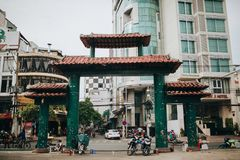 Traditional oriental gates and modern buildings on street of Ho Chi Minh, Vietnam. HO CHI MINH, VIETNAM - 03 JANUARY, 2018: traditional oriental gates and modern royalty free stock photo