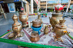 Traditional oriental old metal Samavar for tea drinking and teapots of outdoor cafe. Royalty Free Stock Image