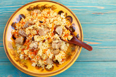 Traditional oriental pilaf, rice with meat and carrot on blue desk Royalty Free Stock Image