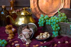 Traditional oriental sweets, nuts and grape. Metal and copper ki Royalty Free Stock Image