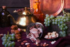 Traditional oriental sweets, nuts and grape. Metal and copper ki. Tchen tools Stock Image