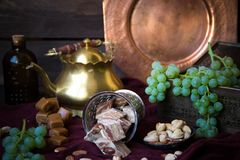 Traditional oriental sweets, nuts and grape. Metal and copper ki. Tchen tools Stock Photo