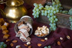 Traditional oriental sweets, nuts and grape. Metal and copper ki. Tchen tools Stock Photography