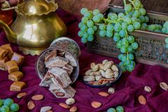 Traditional oriental sweets, nuts and grape. Metal and copper ki. Tchen tools Royalty Free Stock Photos