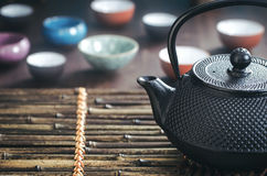 Traditional oriental teapot on bamboo placemat Stock Photography