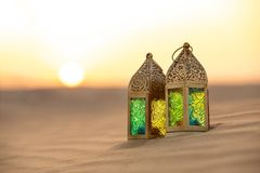 Traditional ornamental arabic candle in desert. Traditional ornamental arabic lantern with a burning candle in desert during sunset. Festive greeting card for Stock Photos