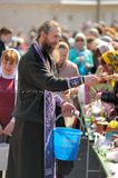 Traditional orthodox paschal ritual - priest blessing easter egg Stock Images