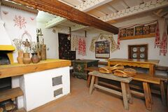 Traditional oven, clay ewers, benches, tables, icons set as a part of interior of Ukrainian rural household