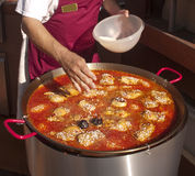 Traditional paella being cooked in large pot Stock Photo