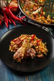 Traditional paella with chicken legs, sausage chorizo and vegeta Stock Photos