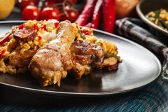 Traditional paella with chicken legs, sausage chorizo and vegetables served on black plate Royalty Free Stock Photos