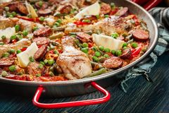 Traditional paella with chicken legs, sausage chorizo and vegetables served in paellera Royalty Free Stock Photo