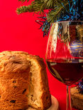 Traditional panettone and glass of red wine under the christmas tree Royalty Free Stock Photography
