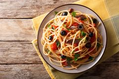 Traditional pasta alla puttanesca with anchovies, tomatoes, garlic and black olives close-up on a plate. horizontal top view. Traditional pasta alla puttanesca royalty free stock image