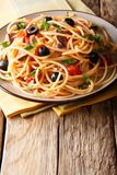 Traditional pasta alla puttanesca with anchovies, tomatoes, garlic and black olives close-up on a plate. vertical. Traditional pasta alla puttanesca with royalty free stock images