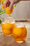 Traditional peach compot in glass jars, healthy preserved dessert Stock Photos