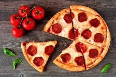 Pepperoni pizza with cut slices, top view table scene over wood. Traditional pepperoni pizza with cut slices. Top view, table scene against a wood background stock photos