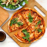 Traditional pizza with fresh arugula. On bamboo board Royalty Free Stock Photo